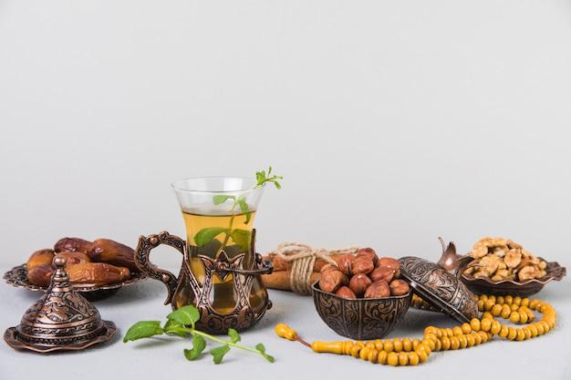 Vaso de té con dátiles frutales, abalorios y frutos secos.