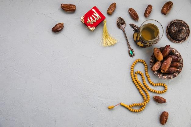 Vaso de té con dátiles frutales y cuentas sobre tabla.