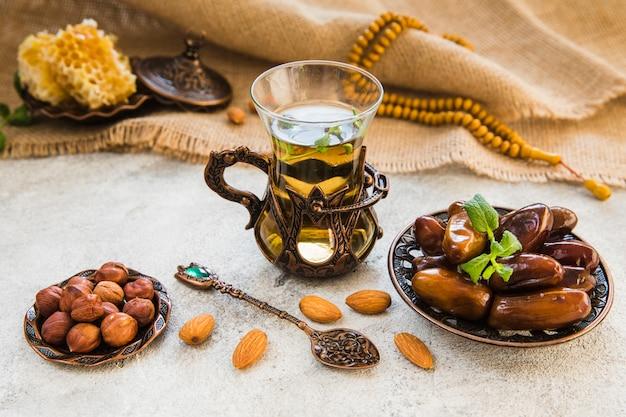 Vaso de té con dátiles frutales y diferentes frutos secos.