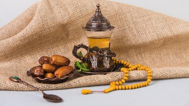 Vaso de té con dátiles frutales y rosario.