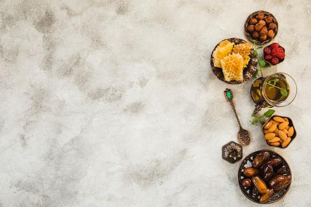 Vaso de té con dátiles frutas y frutos secos.