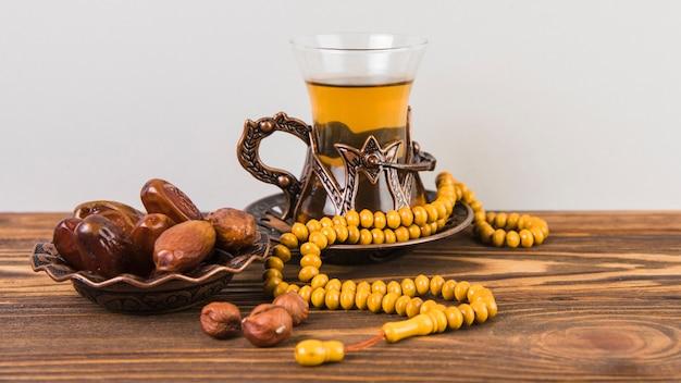Vaso de té con dátiles secos, fruta y rosario.