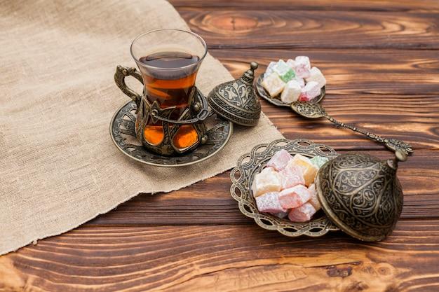 Vaso de té con delicias turcas en mesa