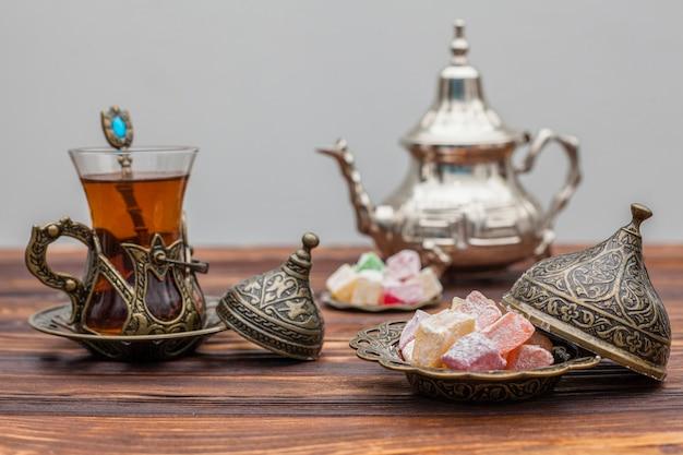 Vaso de té con delicias turcas y tetera