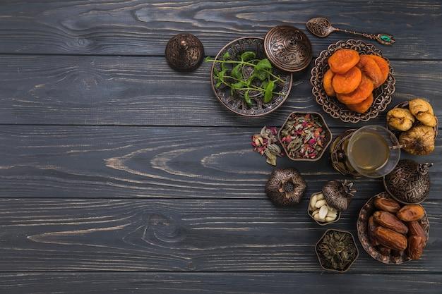 Vaso de té con diferentes frutas secas en mesa