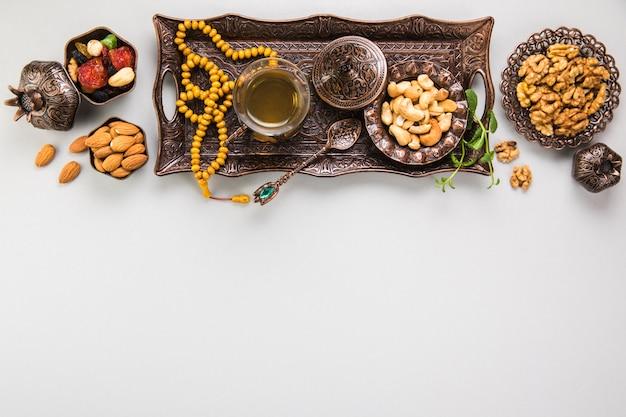 Vaso de té con diferentes frutos secos y cuentas.