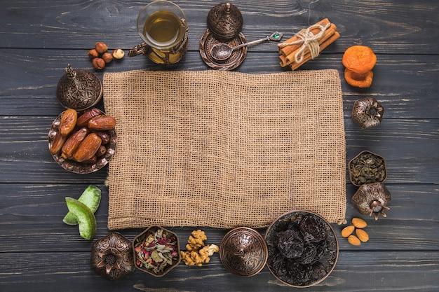 Vaso de té con diferentes frutos secos, nueces y lienzo.