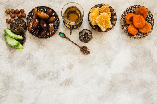 Vaso de té con diferentes frutos secos y panal.
