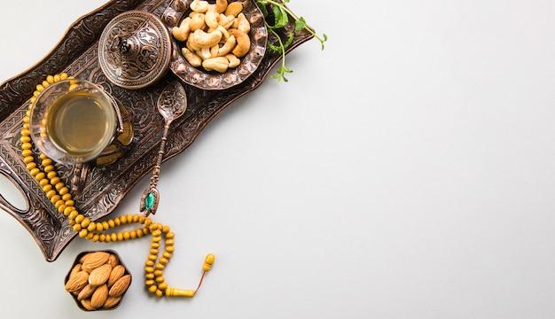 Vaso de té con frutos secos y cuentas en bandeja