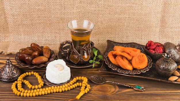 Vaso de té con frutos secos y cuentas en mesa de madera