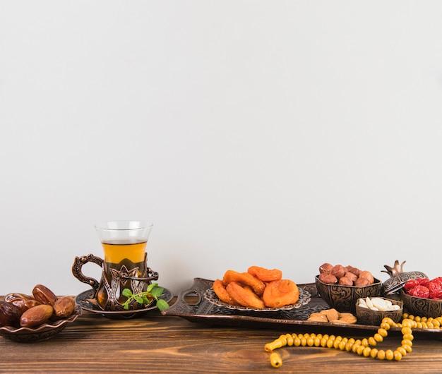 Vaso de té con frutos secos y cuentas en mesa
