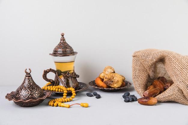 Vaso de té con frutos secos y rosario.