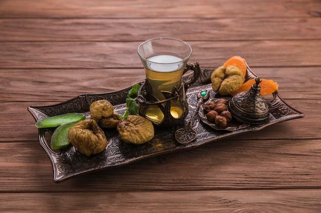 Vaso de té con higos secos y frutos secos.
