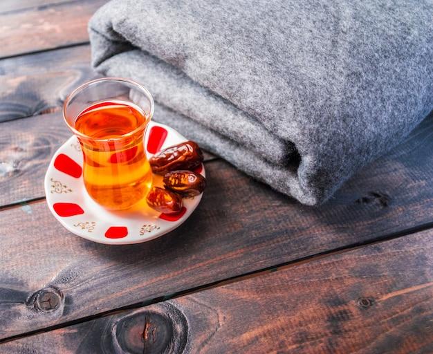Un vaso de té negro y fechas en un plato