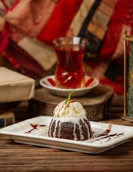 Un vaso de té con pastel de chocolate con crema.