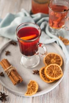 Vaso de té con rodajas de naranja y anís.