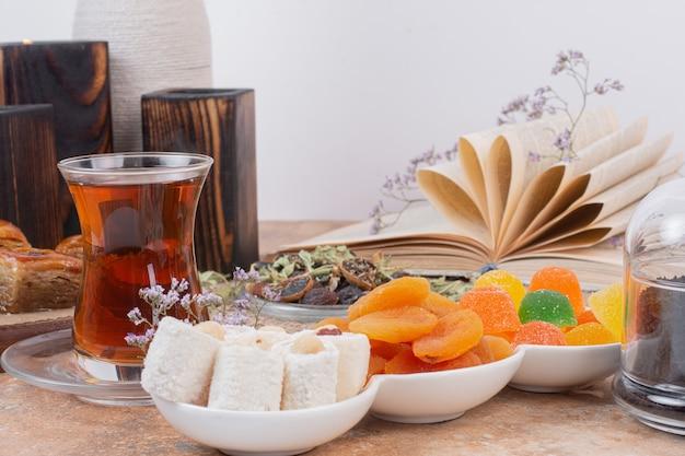 Vaso de té, varios dulces y orejones sobre mesa de mármol.