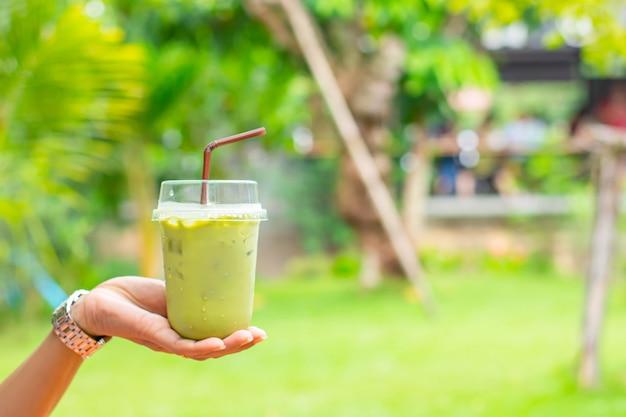 Vaso de té verde frío en la mano, árbol de vistas borrosas.