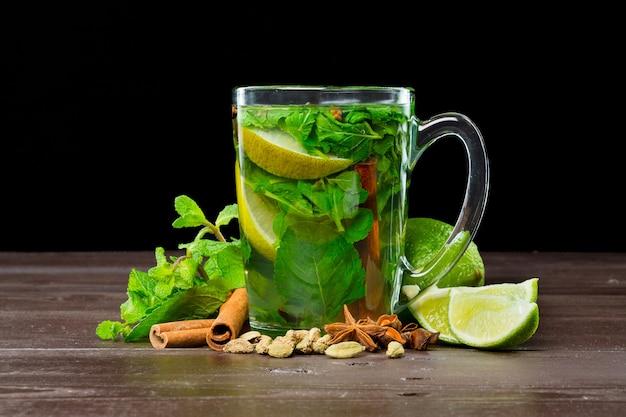 Vaso de té verde con lima, limón, menta