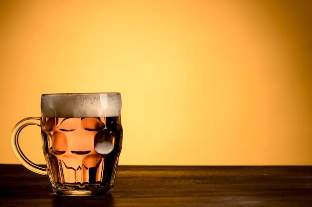 Vaso transparente de cerveza mesa de madera.