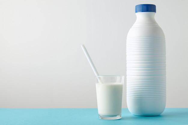 Vaso transparente con leche fresca y pajita blanca en el interior cerca de una botella de plástico en blanco con tapa azul