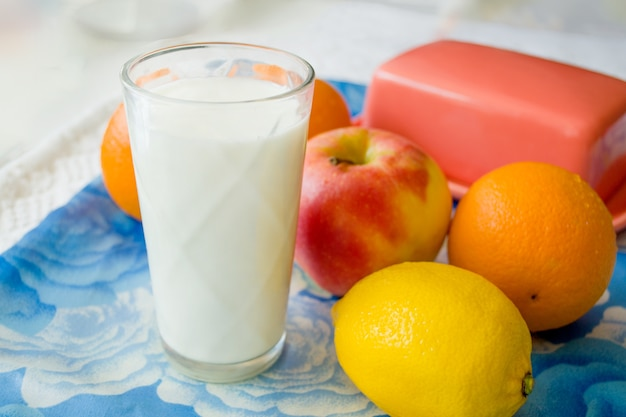 Vaso transparente de leche con un grupo de frutas.