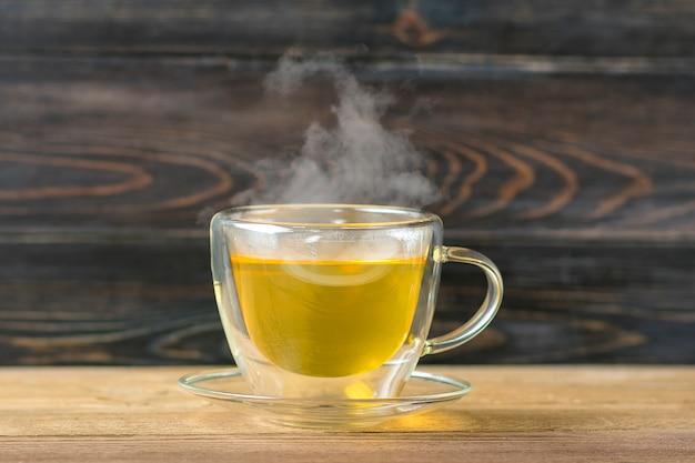 Vaso transparente de té verde caliente con mesa de madera steamon bebida saludable, concepto de bebida antiestrés