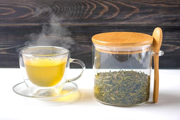 Vaso transparente de té verde caliente con vapor y lata con hojas de té y cuchara en mesa de madera bebida saludable, concepto de bebida antiestrés
