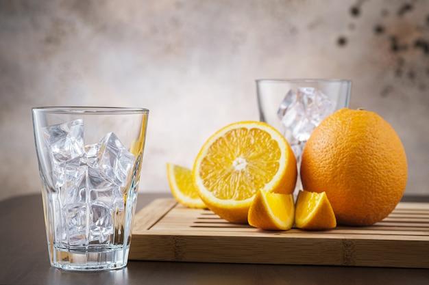 Vaso transparente vacío con cubitos de hielo. en pared de madera con fruta naranja