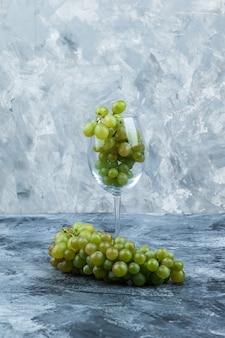 Un vaso de uvas blancas sobre fondo de mármol azul claro y oscuro, primer plano.