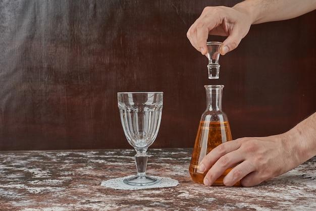 Un vaso vacío y una botella de bebida.