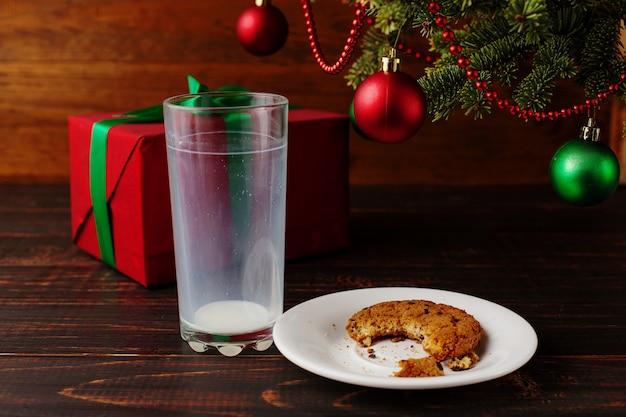 Vaso vacío de galletas de leche y miga y un regalo bajo el árbol de navidad. el de la llegada de santa claus.
