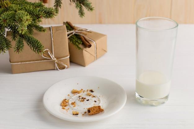 Vaso vacío de galletas de leche y migajas y un regalo debajo del árbol de navidad