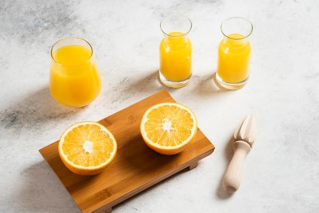 Un vaso de vasos de jugo fresco con rodajas de naranja.