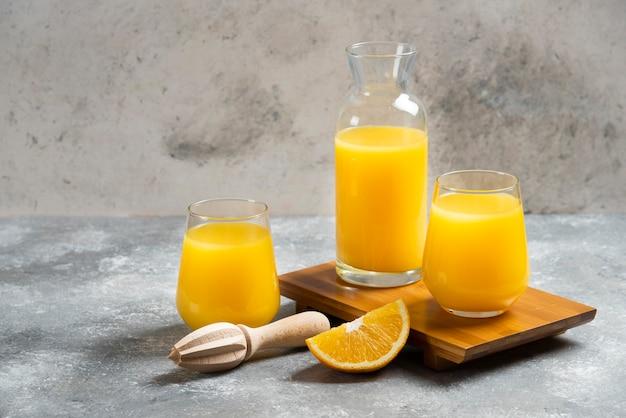 Un vaso de vasos de jugo de naranja y un escariador de madera.