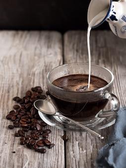 Vaso de vidrio con café, la leche se vierte de un lechero vintage. granos de café sobre una mesa de madera. de cerca.