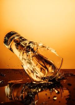 Vaso de vidrio explosivo con agua rompiéndose sobre la superficie naranja