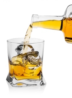 Vaso de vidrio con hielo vierte whisky de botella