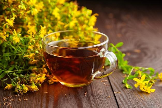 Vaso de vidrio con hypericum perforatum, hierba de san juan o planta tutsan beber con flores frescas en madera oscura.