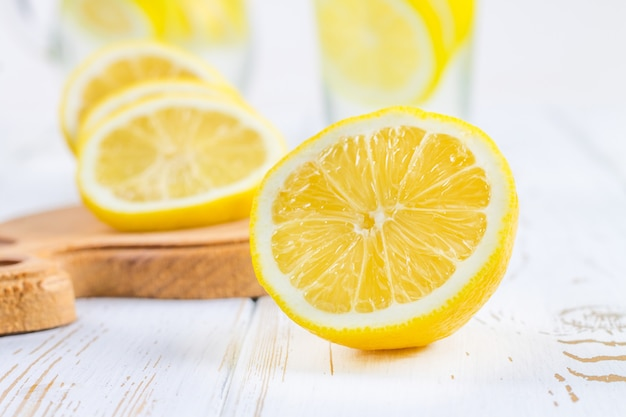 Un vaso de vidrio y una jarra de limonada fría en un fondo blanco de madera rodeado de limones.