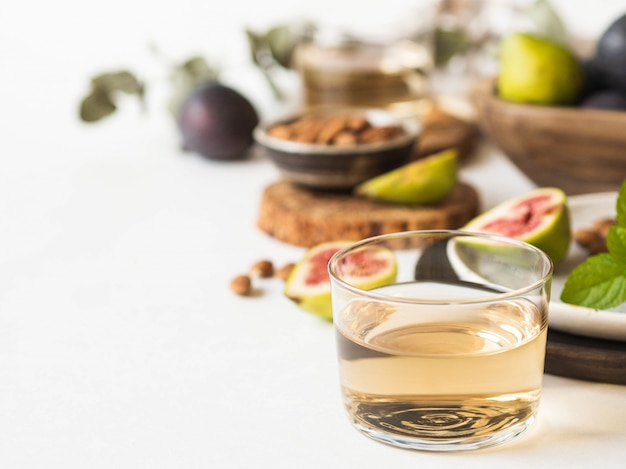 Vaso de vino blanco, higos y almendras sobre un fondo blanco.