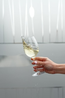 Un vaso de vino blanco en la mano de una mujer.
