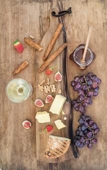 Vaso de vino blanco, tabla de quesos, uvas, higos, fresas, miel y palitos de pan.