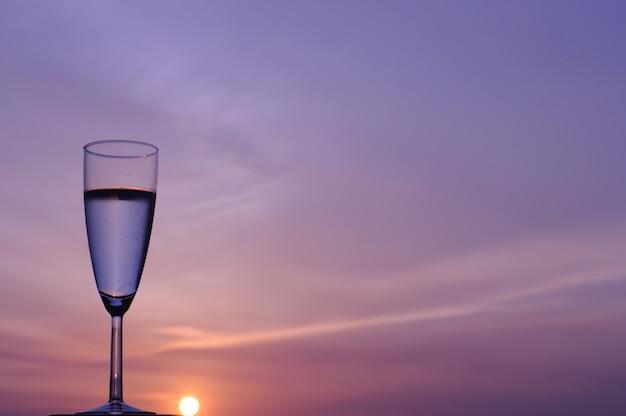 El vaso de vino espumoso aislado en el fondo del cielo al atardecer y el atardecer