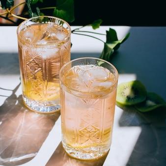 Un vaso de vino rosado en un vaso de cristal sobre mármol, hiedra verde y sol brillante