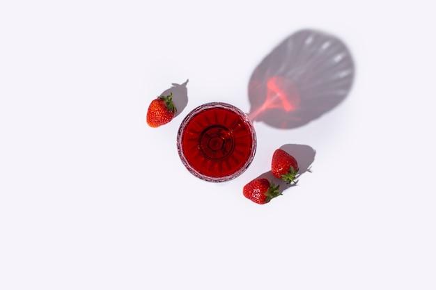 Vaso con vino tinto y fresas sobre la mesa sobre un fondo claro. vista superior, endecha plana