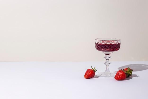 Vaso con vino tinto y fresas sobre la mesa sobre un fondo claro