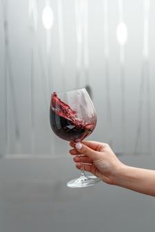 Un vaso de vino tinto en la mano de una mujer.