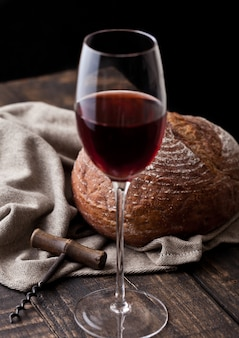 Vaso de vino tinto con pan fresco con sacacorchos retro en la cocina en la mesa de madera