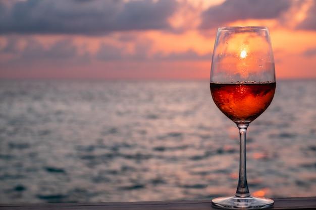 Un vaso de vino tinto en la puesta de sol en las maldivas